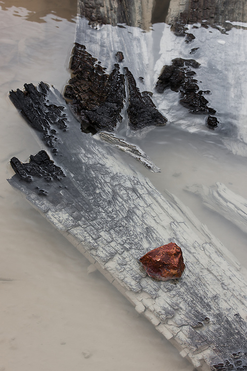 A red rock stands on burnt wood debris on a rainwater puddle. The debris are from the abandoned S. Domingos mine.