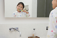Reflection of Young Girl in pyjamas Brushing Her Teeth