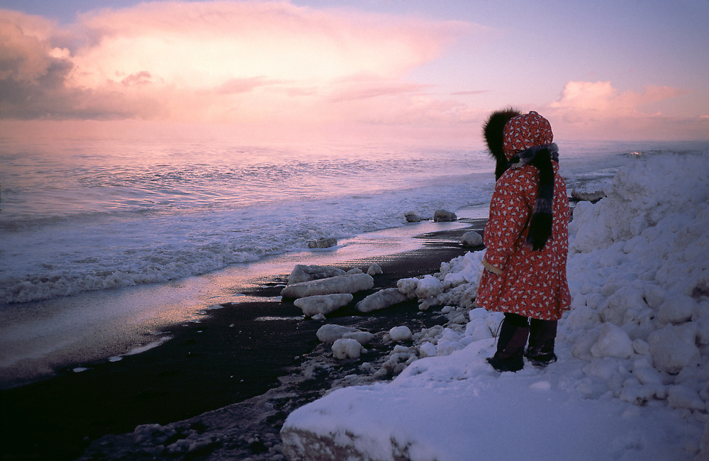 Barrow, Alaska. A native girl looking over the Arctic Ocean sunset while standing on pack ice.