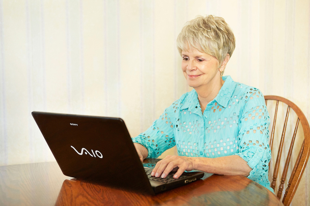 Lifestyle image of woman in her 70s writing email on black Sony Vaio laptop