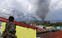 June 27, 2017-  A soldier watches a plume of black smoke billowing from downtown of Marawi City, the Philippines. The Philippine government sticks to its policy of no negotiating with extremists allied with the Islamic State (IS) that overran Marawi City. (Credit Image: © Jeoffrey Maitem/Xinhua via ZUMA Wire)