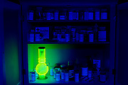 A glowing bong in a well-stocked medicine cabinet at night.Black light