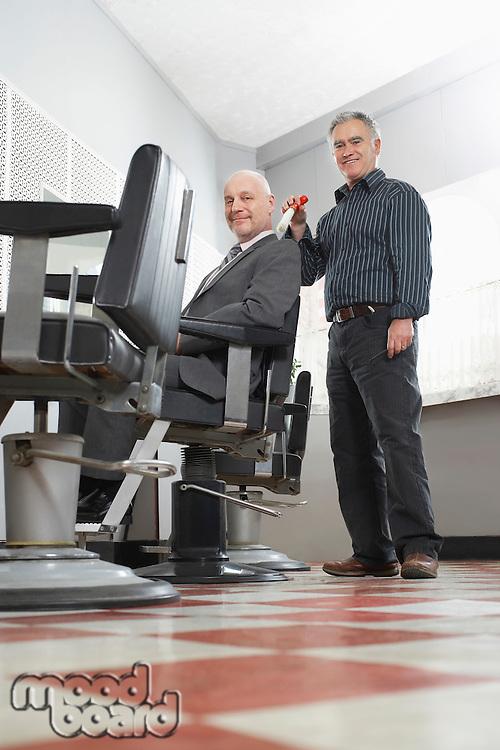 Barber brushing business mans head in barber shop portrait