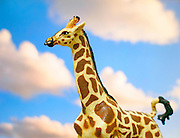 Toy giraffe on cloudy sky background