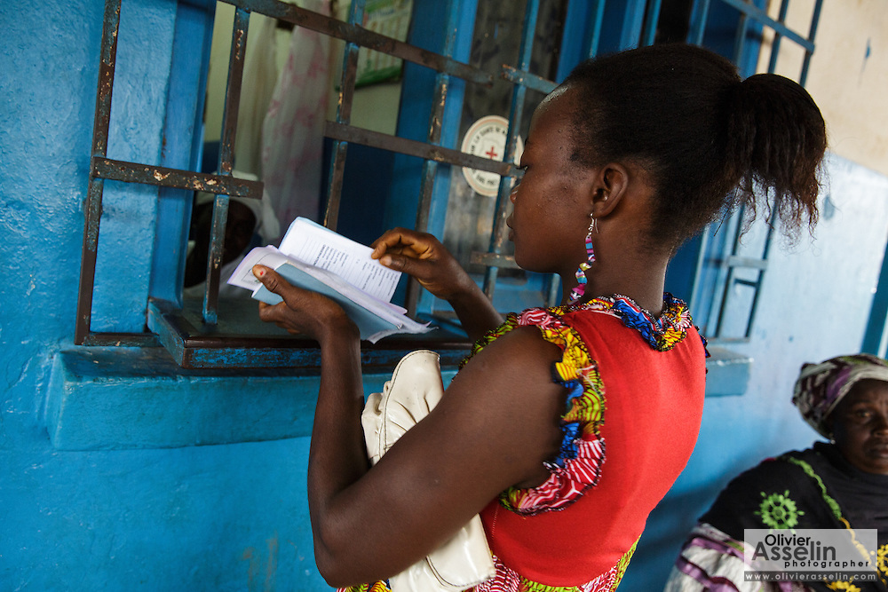 Rita Sahi, 25, who is 7-month pregnant with her third child, hands in her prescription at the pharmacy counter of the Libreville health center in Man, Cote d'Ivoire on Wednesday July 24, 2013.