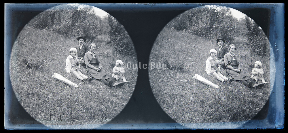 family sitting in the grass on a hill circa 1930s