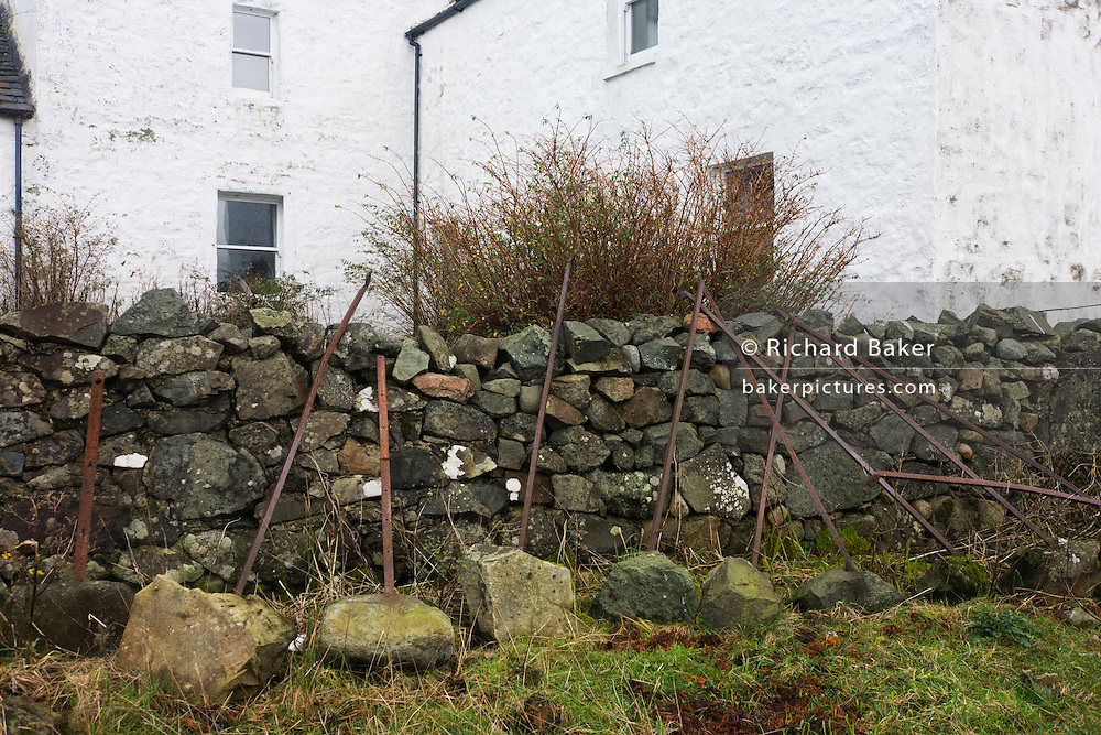 Iron piles lean against a dry stone wall at the rear of Old Ferry House, now a remote self-catering house at Grasspoint, Loch Don, Isle of Mull, Scotland. Highlander effigy on an outside wall of Old Ferry House, now a remote self-catering house at Grasspoint, Loch Don, Isle of Mull, Scotland. (http://www.isleofmullcottages.com/old_ferry_house.htm)