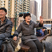 A couple, who were farmers until their farms were destroyed by the government two years ago, returns to the place where their village once stood. They will move into one of the apartments, dubbed &quot;replacement home&quot;. <br /> <br /> China is pushing ahead with a dramatic, history-making plan to move 100 million rural residents into towns and cities over six years &mdash; but without a clear idea of how to pay for the gargantuan undertaking or whether the farmers involved want to move.<br /> <br /> Moving farmers to urban areas is touted as a way of changing China&rsquo;s economic structure, with growth based on domestic demand for products instead of exporting them. In theory, new urbanites mean vast new opportunities for construction firms, public transportation, utilities and appliance makers, and a break from the cycle of farmers consuming only what they produce.<br /> <br /> Urbanization has already proven to be one of the most wrenching changes in China&rsquo;s 35 years of economic reforms. Land disputes rising from urbanization account for tens of thousands of protests each year.
