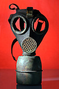 old broken military gas mask against a red back ground