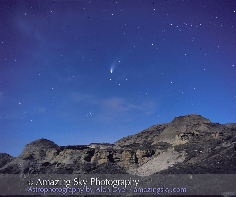 Comet Hale-Bopp over landscape at Dinosaur Privincial park, Alberta, site of world's largest late Cretaceous dinosaur fossil finds. ..Taken in mid-April 1997 with Moon providing illumination. Taken with Plaubel Makina 6x7 camera with 80mm lens at f/2.8 and Ektachrome 400 slide film. About 30 second exposure. on fixed tripod. No tracking.