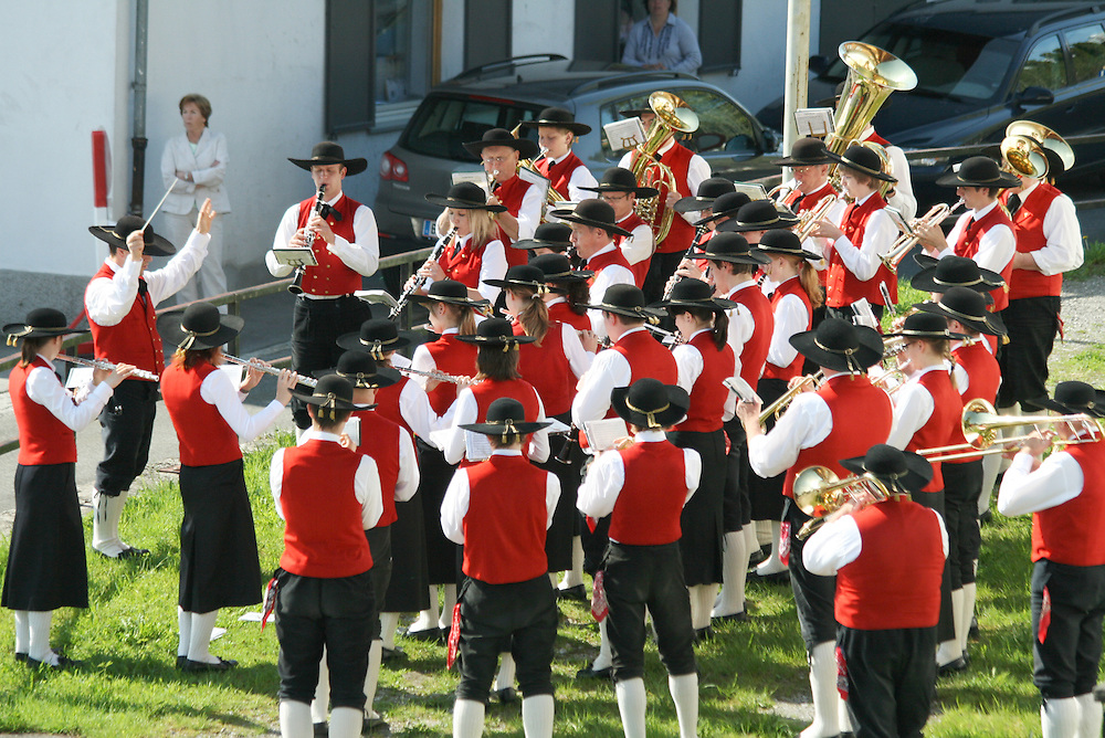 A brass band dressed in traditional Austrian costume pla.ying in the centre of St Anton during a cultural festival