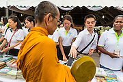 "23 APRIL 2013 - BANGKOK, THAILAND:   Thais place books donated to Thai literacy projects into monks' alms bowls during the opening ceremony to mark Bangkok as the World Book Capital City 2013. UNESCO awarded Bangkok the title. Bangkok is the 13th city to assume the title of ""World Book Capital"", taking over from Yerevan, Armenia. Bangkok Governor Suhumbhand Paribatra announced plans that the Bangkok Metropolitan Administration (BMA) intends to encourage reading among Thais. The BMA runs 37 public libraries in the city and has modernised 14 of them. It plans to build 10 more public libraries every year. Port Harcourt, Nigeria will be the next World Book Capital in 2014.<br /> PHOTO BY JACK KURTZ"