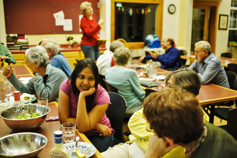 "photo by Matt Roth..Takoma Village Cohousing residents, including Candice Naidoo (an au pair living with a family while going to school), chat during the weekly ""Soup n' Simple"" dinner held in the complex's Common House, Monday, September 24, 2012."
