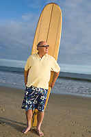 Senior man holding a surfboard