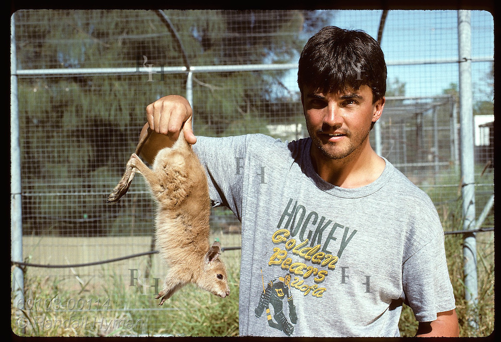 Geoff Lundie-Jenkins holds captive-bred mala(rufous hare-wallaby) @ Conserv Comm of NT;Alice Sprng Australia