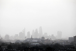 © Licensed to London News Pictures. 07/01/2014. London. UK. King's Cross railway station, with the City of London in background, appear through torrential rain, during another day of heavy rainfall in the UK. Photo: Anna Branthwaite/LNP