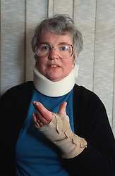 Woman with bandaged wrist wearing neck brace,