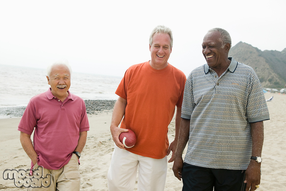 Three senior men walking on beach