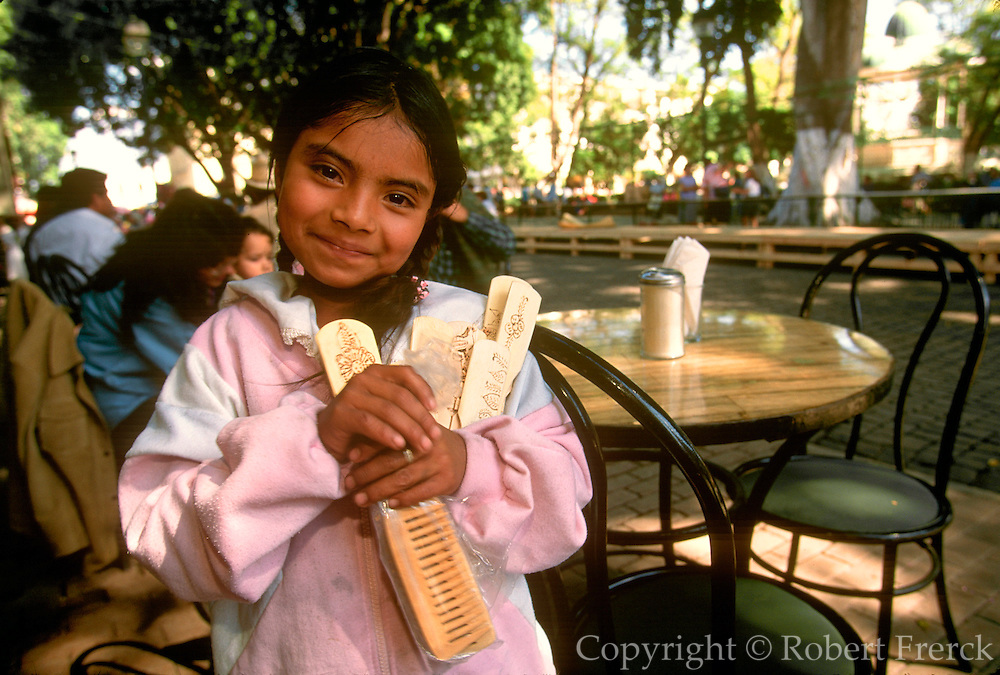 MEXICO, OAXACA, OAXACA STATE Zocalo or main square activity with a little girl selling wood carvings to the tourists