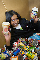 United States, Washington, Seattle, girl (age 9) with cans of food at Hopelink food bank.  MR