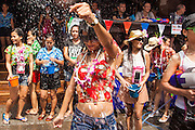 14 APRIL 2013 - BANGKOK, THAILAND:  A woman dances in the midst of a water fight on Sukhumvit Soi Nana on April 14, 2013 in Bangkok, Thailand. The Songkran festival is celebrated in Thailand as the traditional New Year's Day from 13 to 15 April. The throwing of water originated as a way to pay respect to people and is meant as a symbol of washing all of the bad away. PHOTO BY JACK KURTZ