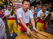 """19 FEBRUARY 2015 - BANGKOK, THAILAND: A man drums for a lion dance troupe on Chinese New Year in Bangkok. 2015 is the Year of Goat in the Chinese zodiac. The Goat is the eighth sign in Chinese astrology and """"8"""" is considered to be a lucky number. It symbolizes wisdom, fortune and prosperity. Ethnic Chinese make up nearly 15% of the Thai population. Chinese New Year (also called Tet or Lunar New Year) is widely celebrated in Thailand, especially in urban areas that have large Chinese populations.    PHOTO BY JACK KURTZ"""