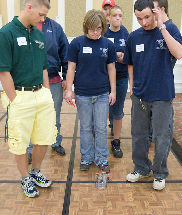 O.U. student Joe Morris (from left), Lacy Kay Morrow and Jeremy Harlow walk behind their battery powered car during the Russ College of Engineering and Technology research fair/engineering day in the Baker Center ballroom on Thursday, 5/3/07.