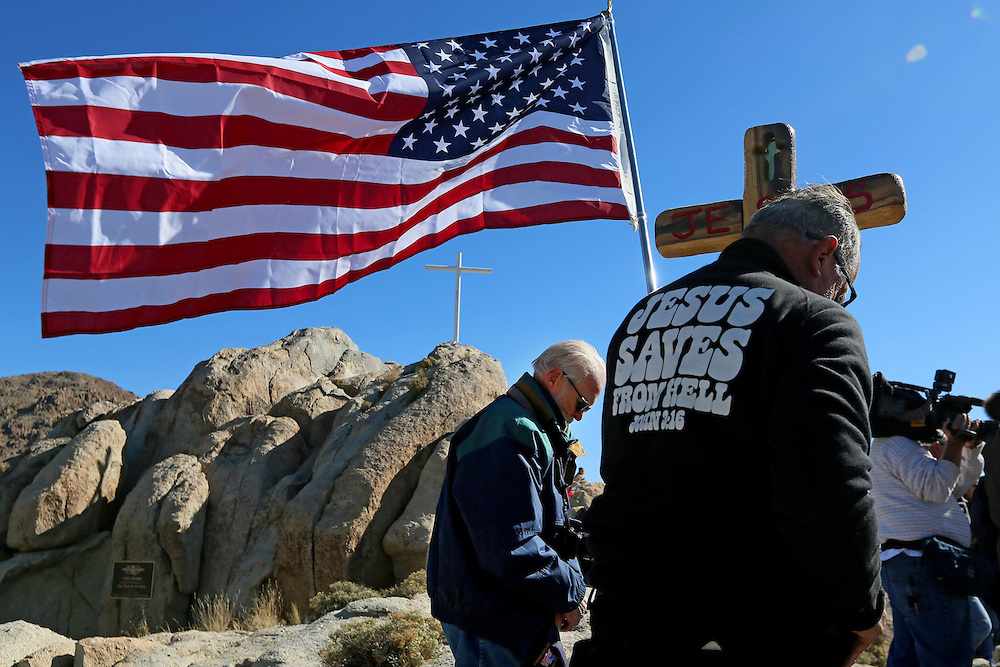 Military Veterans and supporters stand during an unveiling ceremony for the Mojave Cross on Veterans Day in Cima, California on Sunday, November 11, 2012.  A battle has been brewing for over Thirteen years over whether the cross can legally stay on Sunrise Rock because it violates Separation of Church and State and is in the Mojave National Perserve which is on Federal Lands.  The Veterans of Foreign Wars and American Legion Society raised money to purchase the plot of land and has kept the cross in place and today serves as war memorial.(Photo by Sandy Huffaker)