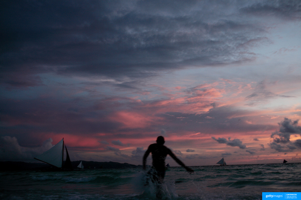A beach scene at dusk at White Beach,  Boracay Island, the Philippines on October 2, 2008, Photo Tim Clayton.....Asian tourists at White Beach, Boracay Island, the Philippines...The 4 km stretch of White beach on Boracay Island, the Philippines has been honoured as the best leisure destination in Asia beating popular destinations such as Bali in Indonesia and Sanya in China in a recent survey conducted by an International Travel Magazine with 2.2 million viewers taking part in the online poll...Last year, close to 600,000 visitors visited Boracay with South Korea providing 128,909 visitors followed by Japan, 35,294, USA, 13,362 and China 12,720...A popular destination for South Korean divers and honeymooners, Boracay is now attracting crowds of tourists from mainland China who are arriving in ever increasing numbers. In Asia, China has already overtaken Japan to become the largest source of outland travelers...Boracay's main attraction is 4 km of pristine powder fine white sand and the crystal clear azure water making it a popular destination for Scuba diving with nearly 20 dive centers along White beach. The stretch of shady palm trees separate the beach from the line of hotels, restaurants, bars and cafes. It's pulsating nightlife with the friendly locals make it increasingly popular with the asian tourists...The Boracay sailing boats provide endless tourist entertainment, particularly during the amazing sunsets when the silhouetted sails provide picture postcard scenes along the shoreline...Boracay Island is situated an hours flight from Manila and it's close proximity to South Korea, China, Taiwan and Japan means it is a growing destination for Asian tourists... By 2010, the island of Boracay expects to have 1,000,000 visitors.