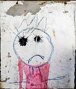 Emoji of a Sad boy naive graffiti painting on a wall