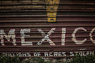 Mexico: Billions of Acres Stolen.  Graffiti in English on the Mexico side of the US-built border wall in Colonia Libertad.  Tijuana, Mexico.