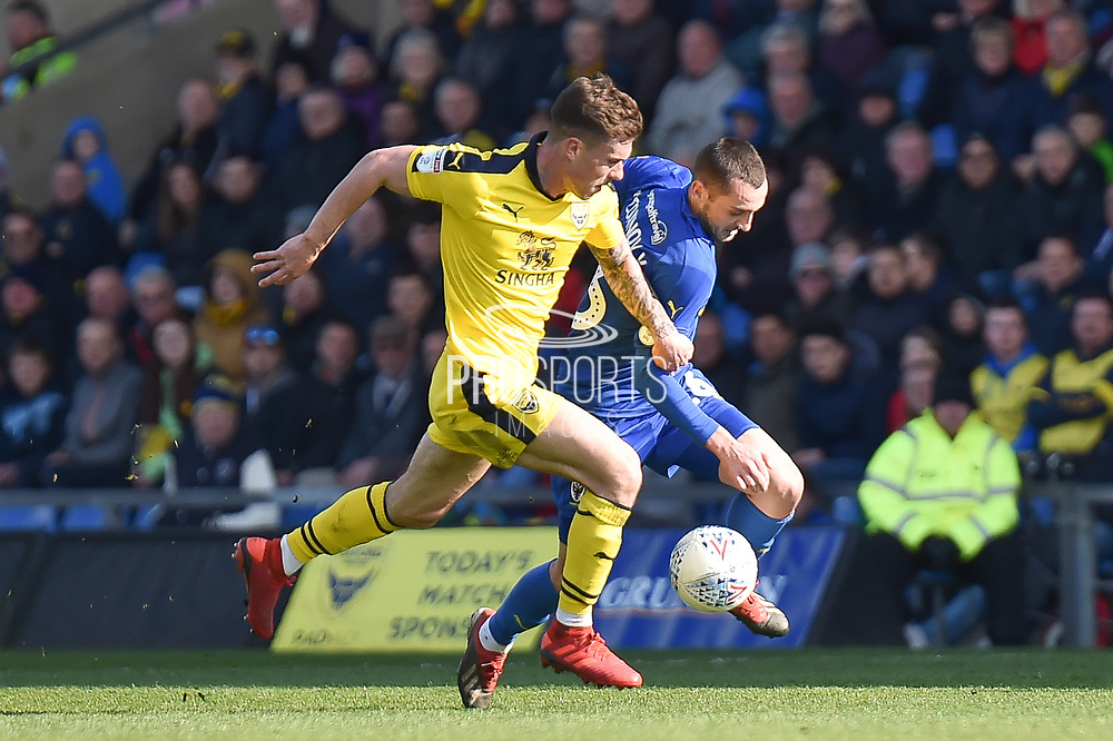 Oxford United midfielder Josh Ruffels (14) battles for possession with AFC Wimbledon midfielder Dylan Connolly (16) during the EFL Sky Bet League 1 match between Oxford United and AFC Wimbledon at the Kassam Stadium, Oxford, England on 13 April 2019.