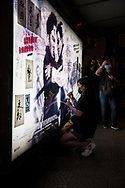 At the end of a protest at Chater Garden in Kong Kong's Central district, where thousands gathered for a #MeToo rally to demand Hong Kong police answer accusations of sexual violence against protesters, a woman uses fingernail polish to add her message to a bus stop billboard. Many other protest-related messages had already been left by others. <br />