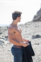 shirtless man holding his shirt at the ocean