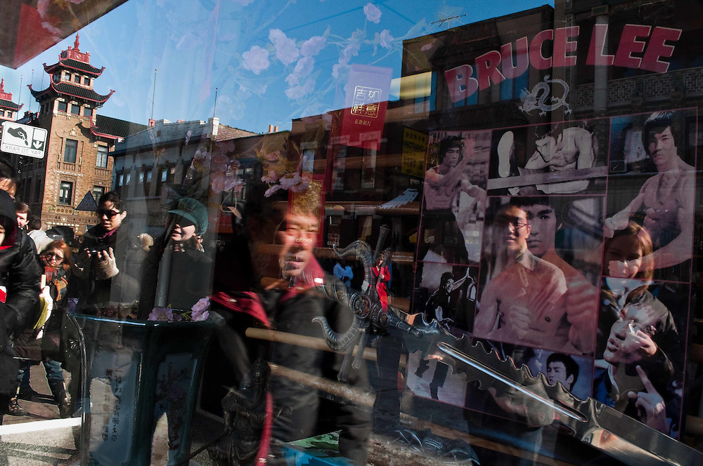 Bruce Lee poster through a window reflecting faces in Chicago's Chinatown during the Chinese New Year Parade, 2010