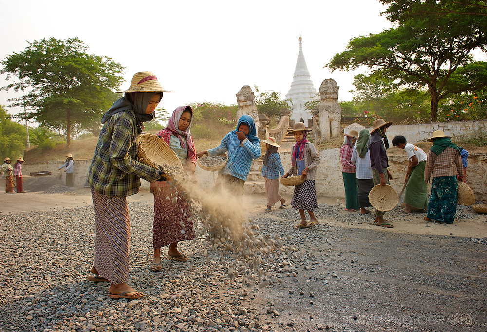 A group of women scatters stones over the freshly tarred area of the road.