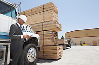 African American male contractor using tablet PC while standing by logging truck