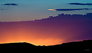 The horizon is awash in color for but a few minutes after the sun sets in the Painted Desert, Arizona.  The Painted Desert encompasses over 93,500 acres, stretching for over 160 miles, and derives its name for the multitude of colors ranging from lavenders to shades of gray with vibrant reds, oranges and pink &ndash; colors observed here in the evening clouds.  The area is a long expanse of badland hills and buttes which, although barren and austere, encompass a rainbow of colors due to the colorful sediments of bentonite clay and sandstone. <br /> <br /> The desert is composed of stratified layers of easily erodible siltstone, mudstone, and shale of the Triassic Chinle Formation. These fine-grained rock layers contain abundant iron and manganese compounds which provide the pigments for the various colors of the region.<br /> <br /> The Painted Desert was named by an expedition under Francisco V&aacute;zquez de Coronado on his 1540 quest to find the Seven Cities of Cibola, which he located some forty miles east of here. Discovering that the cities were not made of gold, Coronado sent an expedition to find the Colorado River for supplies. The group passed through the colorful landscape and named the area &quot;El Desierto Pintado&quot; - The Painted Desert.
