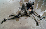 Mud covered couple engaging in a passionate clench at Glastonbury Festival UK 1998