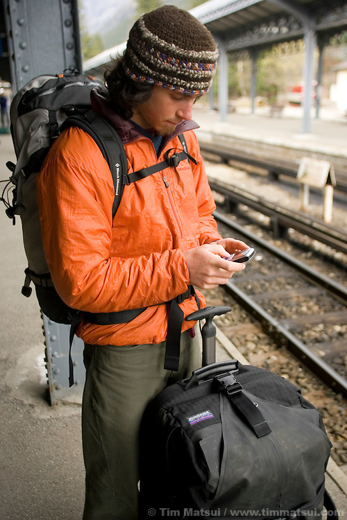 A caucasian male text messages while waiting for the train in  Chamonix, France.