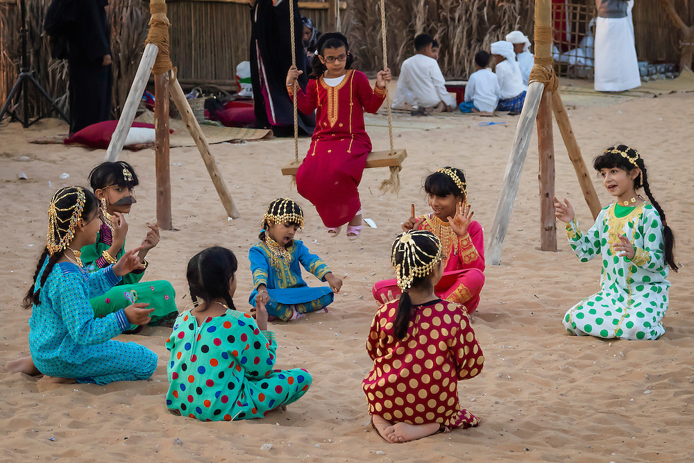A group of Emirati girls dressed in native clothing play and sing in the yard