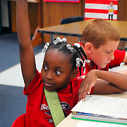 Elementary 3rd grade African American student raising her hand to answer question sitting at their tables in Middleton-Burney Elementary Crescent City FL