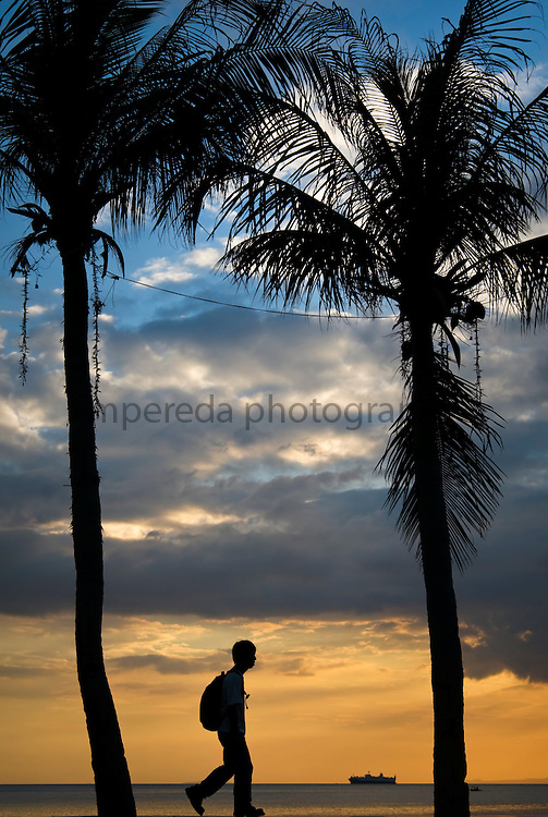 MANILA (Philippines). 2009. A tourist walking in the Roxas Boulevard at dusk.