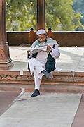 INDIA, OLD DELHI:  East Indian Muslim man reads the newspaper in the courtyard of the Jama Masjid Mosque as he waits for prayer time.