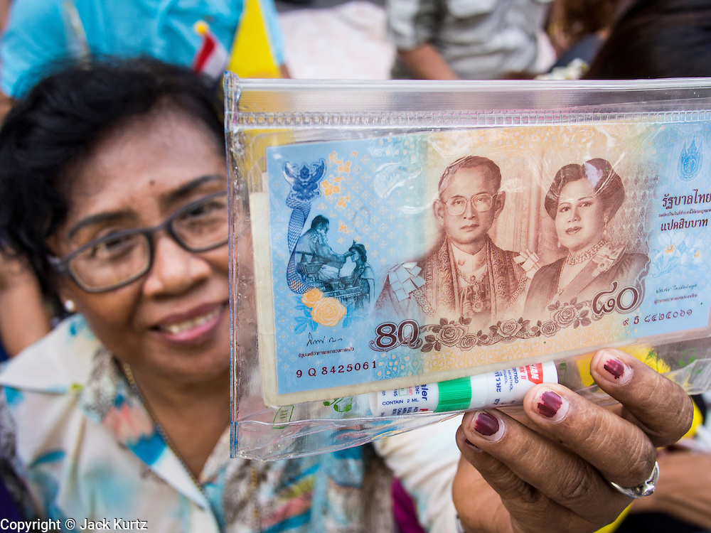 01 AUGUST 2013 - BANGKOK, THAILAND: A woman holds up a limited edition 80Baht Thai currency note (about $2.70US) with a picture of Bhumibol Adulyadej, the King of Thailand, and his wife Queen Sirikit at Siriraj Hospital before the King, 85, was discharged from Bangkok's Siriraj Hospital, Thursday where he has lived since September 2009. He traveled to his residence in the seaside town of Hua Hin, about two hours drive south of Bangkok, with his wife, 80-year-old Queen Sirikit, who has also been treated in the hospital for a year.      PHOTO BY JACK KURTZ