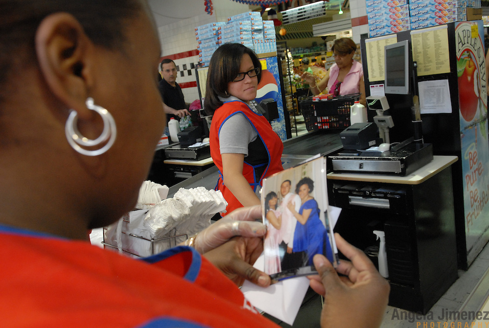 DATE: 6/24/07<br /> DESK: CTY<br /> SLUG: CTOWN<br /> ASSIGN ID: 30044113A<br /> <br /> Geraldine Arvelo, 17, right, of Sunset Park, looks on as a co-worker flips through snapshots from her recent High School of Telecommunication Arts and Technology senior prom during her cashier shift at Steve's C-Town, a grocery store on 9th Street between 5th and 6th Avenues in Park Slope, Brooklyn on June 24, 2007. <br /> <br /> Arvelo went on a double date with her best friend, who she helped get a job at the store as a stockboy, and their dates, also C-Town employees. <br /> <br /> &quot;It's just like high school,&quot; Arvelo says of working at the store. <br /> <br /> Arvelo was born on December 19, 1989.<br /> <br /> <br /> photo by Angela Jimenez for The New York Times<br /> photographer contact 917-586-0916