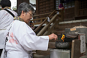 A woman light three sticks of incense, one for the past, one for the present and one for the future.  <br />