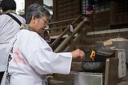 A woman light three sticks of incense, one for the past, one for the present and one for the future.  <br /> <br /> The first temple Ryōzen-ji (霊山寺) of the Shikoku Pilgrimage, 88 temples associated with the Buddhist monk Kūkai (Kōbō Daishi) on the island of Shikoku, Naruto,Tokushima Prefecture, Japan<br /> <br /> <br /> En kvinna t&auml;nder tre r&ouml;kelser, en f&ouml;r det f&ouml;rg&aring;ngna, en f&ouml;r nuet och en f&ouml;r framtiden. <br /> Tempel nummer 1, Ryōzen-ji (霊山寺)<br /> <br /> Pilgrimsvandring till 88 tempel p&aring; japanska &ouml;n Shikoku till minne av den japanske munken Kūkai (Kōbō Daishi). <br /> <br /> Fotograf: Christina Sj&ouml;gren<br /> Copyright 2018, All Rights Reserved