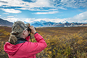 A visitor uses binoculars to get a better look at the mountains in Denali National Park, Alaska.