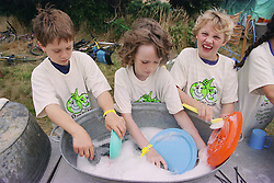 Group of children washing up plates outside in campsite during environmental awareness camp,